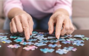A senior woman doing a puzzle to help maintain and improve cognitive functions