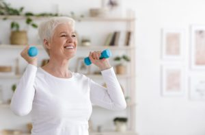 Smiling senior lady exercising with dumbbells to live a healthy, active lifestyle