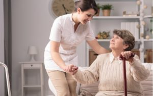 Elderly woman smiling up at a caregiver while receiving assisted care