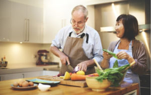 Elderly couple cooking a healthy meal for themselves to ensure proper nutrition