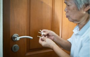 Senior woman having difficulty remembering which key is correct to open her front door to her home